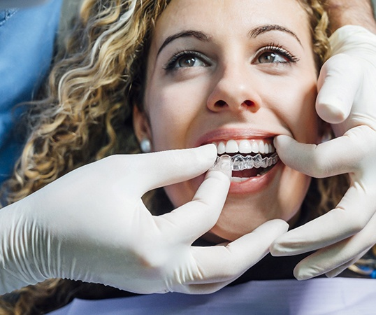 Dentist putting ClearCorrect tray on patient