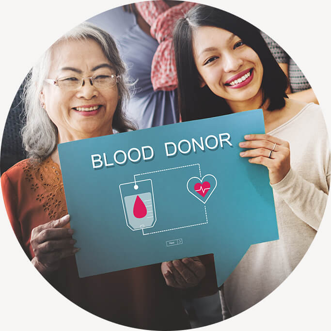 Two smiling people holding blood donor sign