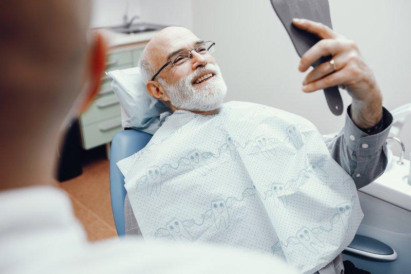 Older man checking new dentures in handheld mirror