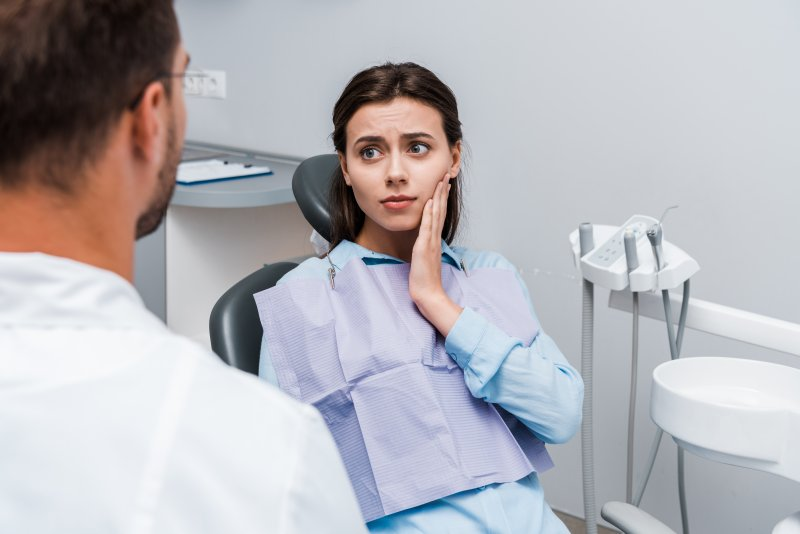 Concerned woman talking to emergency dentist about toothache